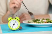 Alarm clock and dietary food on table close-up