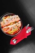 fresh fried natural pink salmon on italian traditional tagliatelles backed with tomato and vegetables served over black wooden table