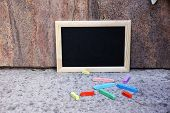 Rectangular blackboard and pieces of chalk in front of the wall