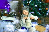 picture of knitted cap  - the girl in lilac jeans in a knitted cap and with a knitted scarf sits on a sledge near a Christmas fir - JPG