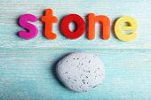 Stone word formed with colorful letters on wooden background