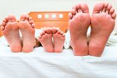 Family Of Three People Sleeping In One Bed, Feet Close-up