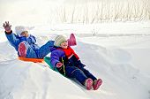stock photo of snow-slide  - Two little girls on a sled sliding down a hill on snow in winter - JPG