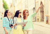 tourism, travel, leisure, holidays and friendship concept - smiling teenage girls with map and camera outdoors