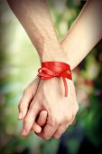 Man's and woman's hands tied with ribbon on bright background