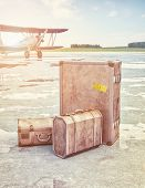 Vintage suitcases and retro airplane on runway. 3d concept
