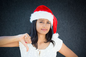 picture of pissed off  - Closeup portrait of unhappy pissed off christmas woman with red hat thumbs down sign disgusted negative human facial expression isolated on grey black background - JPG