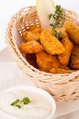picture of high calorie foods  - Crispy fried crumbed chicken nuggets in a wicker basket served as a finger food or appetizer with a creamy dip in a bowl alongside