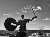 foto of viking  - Medieval viking warrior wearing chainmail he has the sword and the shield north nature on background black and white image - JPG