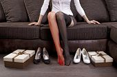 stock photo of ankle shoes  - lady trying on several pairs of shoes in the mall - JPG