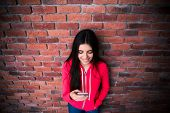 picture of sportive  - Happy woman using smartphone over brick wall - JPG