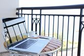 picture of telecommuting  - Computer laptop on balcony with sea view and coffee and pen - JPG
