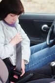 stock photo of seatbelt  - Woman putting on a seatbelt for safety  - JPG