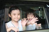 Boy & Girl Waving In The Car
