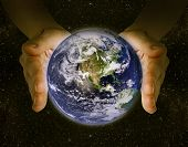 foto of save earth  - man holding the planet earth in the hands against the background of the galaxy - JPG
