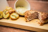 picture of beef-burger  - Succulent cooked beef burger with potato on a wood plate. ** Note: Shallow depth of field - JPG