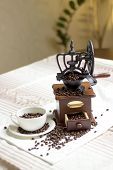 picture of coffee coffee plant  - white tablecloth on the table or burlap old coffee grinder filled with coffee beans next to a white porcelain cup filled with coffee beans two croissants - JPG