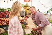 stock photo of farmers market vegetables  - Woman Buying Fresh Vegetables At Farmers Market Stall - JPG