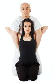 stock photo of thai massage  - Young female receiving massage from therapist in traditional thai position looking at camera - JPG