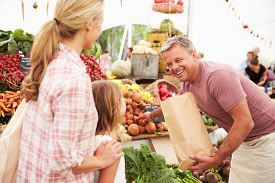stock photo of stall  - Family Buying Fresh Vegetables At Farmers Market Stall - JPG
