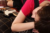 young beautiful woman with a bass guitar - asleep