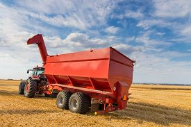 pic of tractor-trailer  - Agricultural tractor with a trailer waiting to be fully loaded with harvested golden cereal grains by a com - JPG