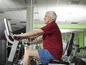 Senior man spinning on fitness bike in fitness center poster