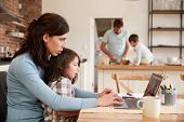 Busy Family Home With Mother Working As Father Prepares Meal poster