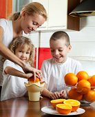 Happy mother with children squeezed orange juice