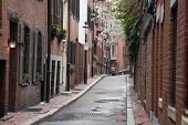 stock photo of brownstone  - A quaint narrow city street lined with brownstone row houses - JPG