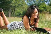 Young African American Female Reading Book Outdoor in Summer