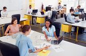 Three women working together in a busy office, elevated view poster