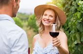 Senior woman with straw hat holding wine glass and looking at camera. Winegrowers at wineyard tastin poster