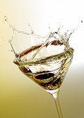 martini cocktail splashing on yellow background