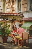Young Beautiful Happy Loving Couple Sitting At Street Open-air Cafe Looking At Each Other. Beginning poster