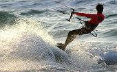 Kitesurfer make wave and splashes on water during his training on Mediterranean sea.