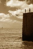 Teenagers jumping from the wall of ancient fortress in to Mediterranean Sea in Acre, Israel (sepia toned).