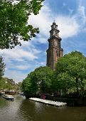 View on Amstel river and Westerkerk church (western church) in Amsterdam, Netherlands.