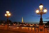 PARIS - JULY 10: Famous Eiffel Tower with night illumination and beautiful lampposts on Alexander th
