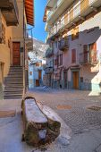 Vertical oriented image of small street among colorful houses in Limone Piemonte town in northern It