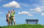 senior retired smiling couple, man greeting with his hand, walking outdoors on green grass hill with