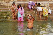 hindu man pouring water in holy river ganges in varanasi