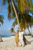 Happy senior couple on the beach greeting with their hands, enjoying retirement on tropical destination: Maria la Gorda on caribbean island Cuba poster