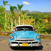 European senior couple having fun touring around Vinales valley, Cuba, in an vintage old-timer car