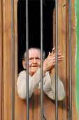 CAMAGUEY, CUBA - CIRCA NOVEMBER 2008 : An old lady behind bars in her home in the city of Camaguey, Cuba circa November 2008. The town was designated a UNESCO World Heritage Site in July 2008.