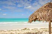 Palm leaf umbrella on tropical beach of Cayo las Brujas on caribbean island Cuba