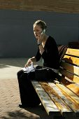 Young Woman Doing Paperwork On Park Bench