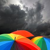 Rainbow colored umbrellas and dark cloudy sky in autumn time on square background