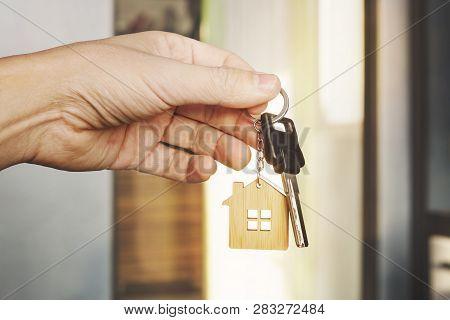 poster of House Key In Male Hand At Apartment Background. House Key Ring. Concept Of Moving In New Living Apar