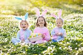 Kids With Bunny Ears On Easter Egg Hunt. poster